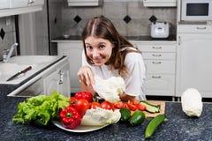 Cocinero de sexo femenino joven que hace una ensalada fresca con las verduras orgánicas Imagenes de archivo