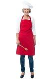 Cocinero de sexo femenino mayor alegre con la cuchara fotos de archivo libres de regalías