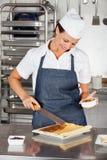 Cocinero de sexo femenino Preparing Chocolate Roll Fotografía de archivo libre de regalías