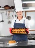 Cocinero de sexo femenino Presenting Baked Breads Imágenes de archivo libres de regalías