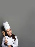 Cocinero de sexo femenino que cocina pensando qué cocinar Imágenes de archivo libres de regalías