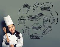 Cocinero de sexo femenino que cocina pensando qué cocinar Fotos de archivo