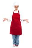 Cocinero de sexo femenino que le acoge con satisfacción con una sonrisa imágenes de archivo libres de regalías
