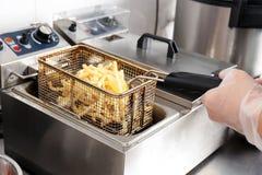Cocinero de sexo femenino que prepara las patatas fritas foto de archivo libre de regalías