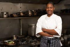 Cocinero de sexo femenino que se coloca al lado de la cocina Imagenes de archivo