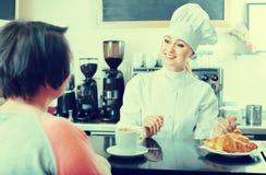 Cocinero de sexo femenino que sirve un postre al cliente en el café Imagen de archivo