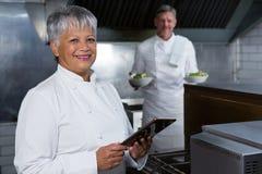Cocinero de sexo femenino que sostiene la tableta digital Foto de archivo libre de regalías