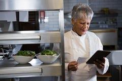 Cocinero de sexo femenino que sostiene la tableta digital Fotografía de archivo libre de regalías