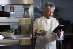 Cocinero de sexo femenino que sostiene la tableta digital Imágenes de archivo libres de regalías