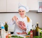 Cocinero de sexo femenino que trabaja con la carne de cabras en cocina Fotografía de archivo libre de regalías