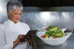 Cocinero de sexo femenino que usa la tableta digital Fotografía de archivo libre de regalías