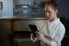 Cocinero de sexo femenino que usa la tableta digital Fotos de archivo libres de regalías