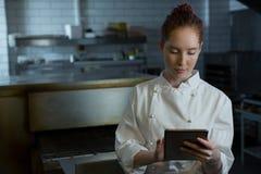 Cocinero de sexo femenino que usa la tableta digital Imagenes de archivo