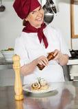 Cocinero de sexo femenino Seasoning Dish With Peppermill Imágenes de archivo libres de regalías