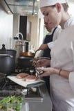 Cocinero de sexo femenino Seasoning Raw Meat en cocina Imagen de archivo