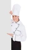 Cocinero de sexo femenino Showing Blank Placard imágenes de archivo libres de regalías