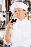 Cocinero de sexo femenino Smelling Red Wine Foto de archivo