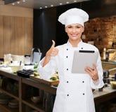 Cocinero de sexo femenino sonriente con el ordenador de la PC de la tableta Foto de archivo