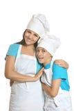 Cocinero de sexo femenino sonriente con los ayudantes Fotografía de archivo