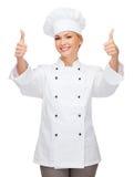 Cocinero de sexo femenino sonriente que muestra los pulgares para arriba Imagenes de archivo