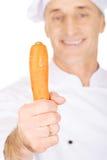 Cocinero de sexo masculino con una zanahoria Fotografía de archivo