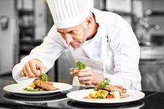 Cocinero de sexo masculino concentrado que adorna la comida en cocina fotografía de archivo libre de regalías
