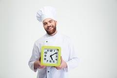 Cocinero de sexo masculino de risa del cocinero que sostiene el reloj de pared Foto de archivo libre de regalías