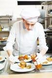 Cocinero de sexo masculino del cocinero que adorna la comida en la placa Fotos de archivo libres de regalías