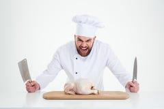Cocinero de sexo masculino del cocinero que se coloca con los cuchillos y el pollo imagen de archivo libre de regalías