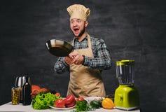 Cocinero de sexo masculino del cocinero que prepara comidas en una cacerola Foto de archivo libre de regalías
