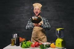 Cocinero de sexo masculino del cocinero que prepara comidas en una cacerola Imagen de archivo libre de regalías