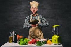 Cocinero de sexo masculino del cocinero que prepara comidas en una cacerola Fotografía de archivo