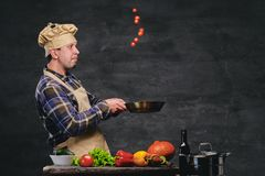 Cocinero de sexo masculino del cocinero que prepara comidas en una cacerola Fotos de archivo