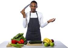 Cocinero de sexo masculino desorientado en un fondo blanco fotos de archivo