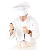 Cocinero de sexo masculino enojado con el pollo sin procesar Fotos de archivo