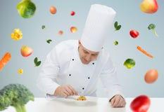 Cocinero de sexo masculino feliz del cocinero que adorna el plato foto de archivo