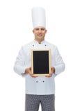 Cocinero de sexo masculino feliz del cocinero que lleva a cabo el tablero en blanco del menú Fotos de archivo libres de regalías