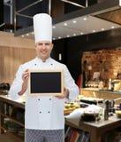 Cocinero de sexo masculino feliz del cocinero que lleva a cabo el tablero en blanco del menú Foto de archivo