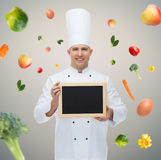 Cocinero de sexo masculino feliz del cocinero que lleva a cabo el tablero en blanco del menú Fotografía de archivo