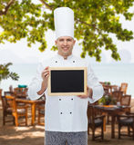 Cocinero de sexo masculino feliz del cocinero que lleva a cabo el tablero en blanco del menú Fotos de archivo
