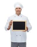 Cocinero de sexo masculino feliz del cocinero que lleva a cabo el tablero en blanco del menú Foto de archivo libre de regalías