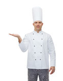 Cocinero de sexo masculino feliz del cocinero que muestra la palma vacía Foto de archivo