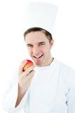 Cocinero de sexo masculino feliz que celebra una manzana y una sonrisa rojas Imagenes de archivo