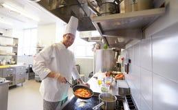 Cocinero de sexo masculino feliz que cocina la comida en la cocina del restaurante imágenes de archivo libres de regalías
