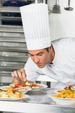 Cocinero de sexo masculino Garnishing Pasta Dishes Imagenes de archivo