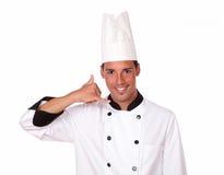 Cocinero de sexo masculino hermoso con gesto de la llamada Imagenes de archivo