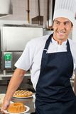 Cocinero de sexo masculino Holding Baked Cake en cocina Imagen de archivo