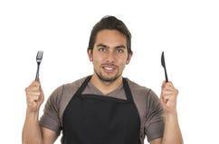 Cocinero de sexo masculino joven hermoso que lleva el delantal negro Fotografía de archivo libre de regalías