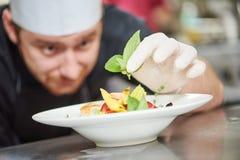 Cocinero de sexo masculino que adorna el plato Foto de archivo