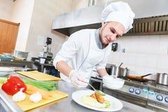 Cocinero de sexo masculino que adorna la placa de la comida Fotografía de archivo